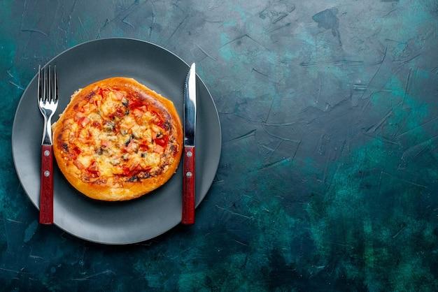Widok z góry małej okrągłej pizzy z serem uformowanej sztućcami na ciemnoniebieskiej powierzchni