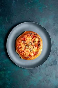 Widok z góry małej okrągłej pizzy z serem uformowanej wewnątrz płyty na ciemnoniebieskiej powierzchni