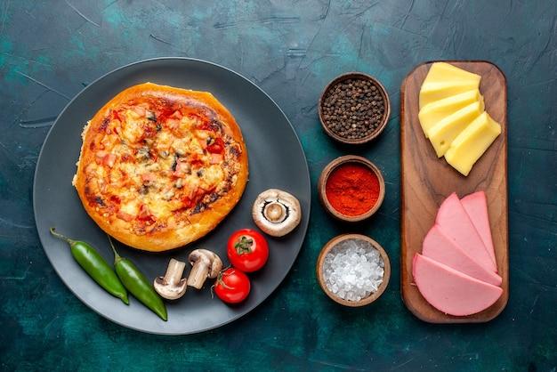 Widok z góry małej okrągłej pizzy z serem uformowanej z przyprawami i serem na ciemnoniebieskiej powierzchni