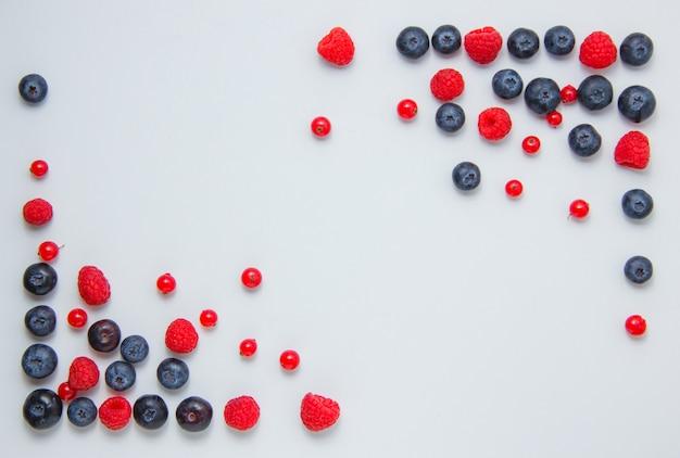Widok z góry malin w rogach z jagodami, czerwonych porzeczek na białym tle. poziomy