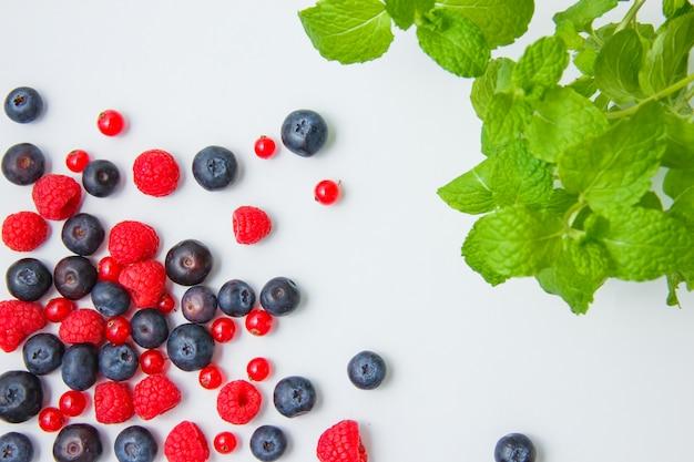 Widok z góry malin z jagodami, czerwonych porzeczek, liści mięty na białym tle. poziomy