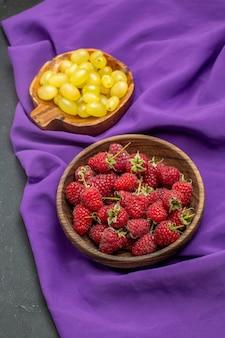 Widok z góry maliny żółte winogrona w miseczkach na purpurowym szal na ciemnej powierzchni