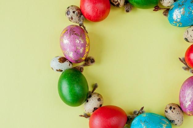Widok z góry malowane jaja wielkanoc ramki w kształcie koła na żółtym tle. skopiuj miejsce
