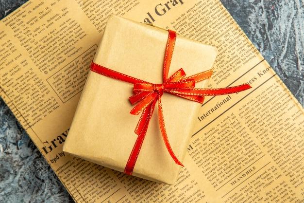 Widok z góry mały prezent związany z czerwoną wstążką na gazecie na ciemnej powierzchni