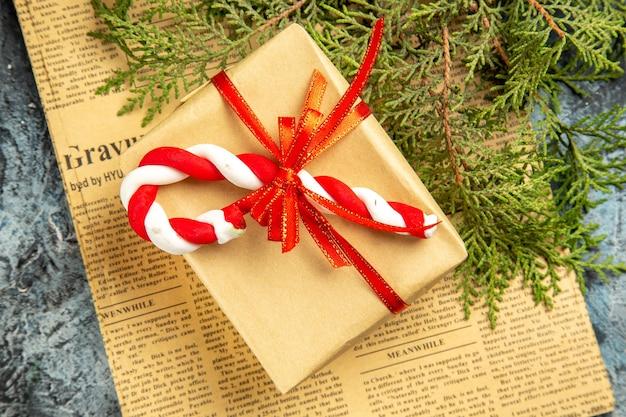 Widok z góry mały prezent związany z czerwoną wstążką świąteczny cukierek na gazetowych gałęziach sosny na szarej powierzchni