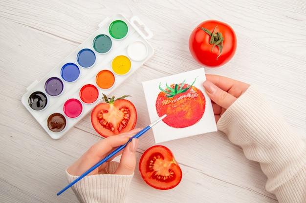 Widok z góry mały rysunek pomidora z pomidorami i kolorowymi farbami na białym stole