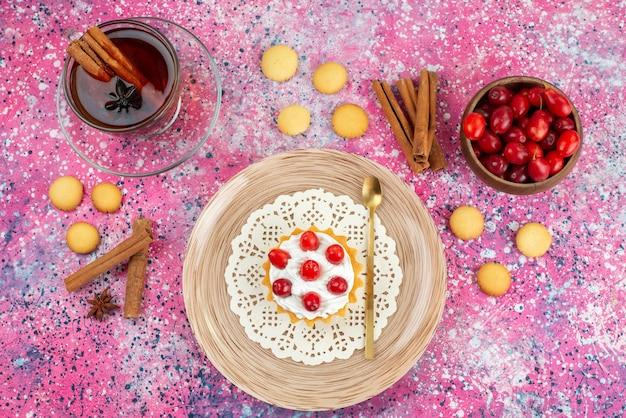 Widok z góry mały tort ze świeżą śmietaną i świeżymi owocami wraz z cynamonem i filiżanką herbaty na jasnym biurku tort ze słodkim cukrem