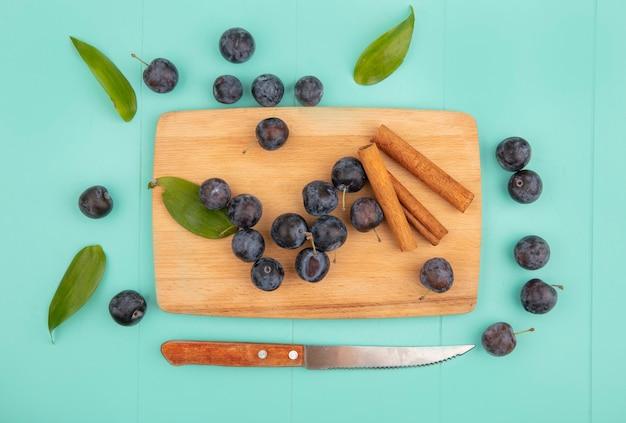 Widok z góry małych kwaśnych czarniawych owoców tarniny na drewnianej desce kuchennej z laskami cynamonu z nożem na niebieskim tle