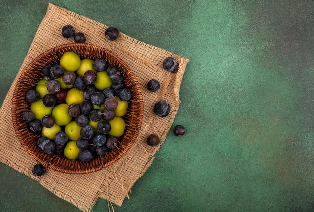 Widok z góry małych kwaśnych niebiesko-czarnych tarn owocowych z zieloną śliwką wiśniową na wiadrze na worku na zielonym tle z miejscem na kopię
