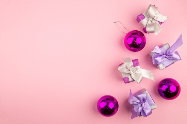 Widok z góry małych prezentów z zabawkami choinkowymi na różowej powierzchni