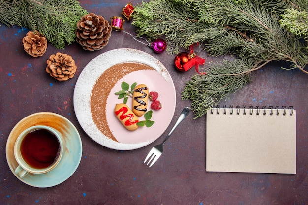 Widok z góry małych słodkich herbatników wewnątrz zaprojektowanego talerza na czarnym stole