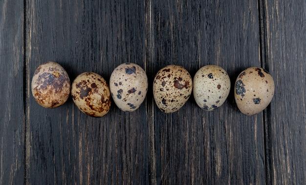 Widok z góry małych świeżych jaj przepiórczych ułożonych w linii na drewnianym tle
