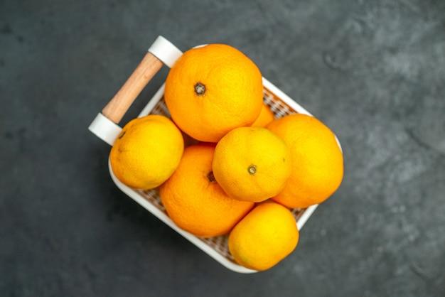 Widok z góry mandarynki i pomarańcze w plastikowym koszu na ciemnym tle