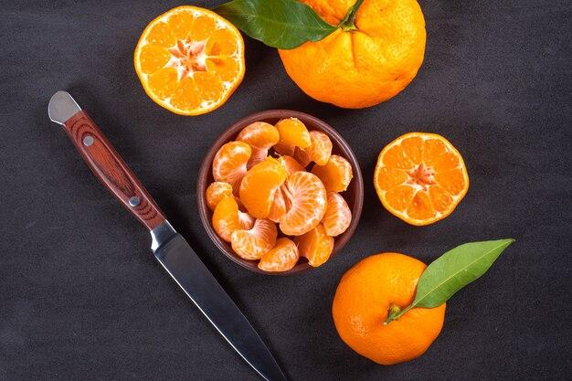 Widok z góry mandarynki w talerzu z nożem
