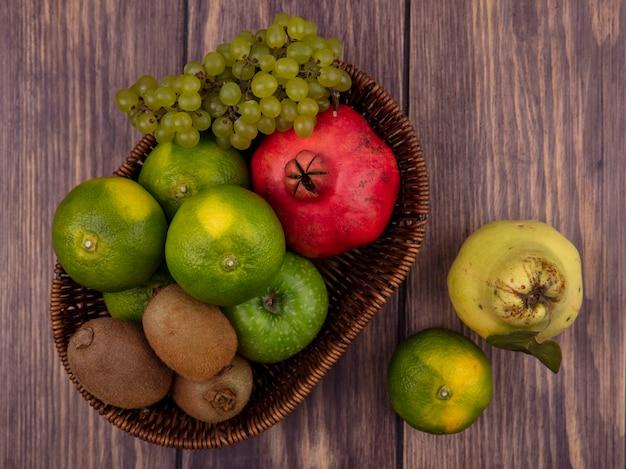Widok z góry mandarynki z granatem gruszka kiwi i winogronami w koszu