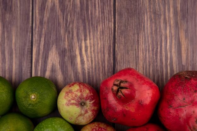 Widok z góry mandarynki z jabłkami i granatem na drewnianej ścianie