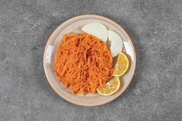 Widok z góry marchewki w puszkach z plasterkami cytryny i cebuli na talerzu