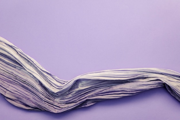 Widok z góry marszczonej tkaniny na fioletowym tle. delikatny połyskliwy jedwab lub tkanina syntetyczna o chrupiącej fakturze, miejsce na kreatywne projektowanie mody, tapety, pocztówki