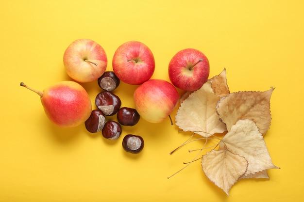 Widok z góry martwa jesień. jabłka, gruszki, opadłe liście, kasztany na żółtym stole.