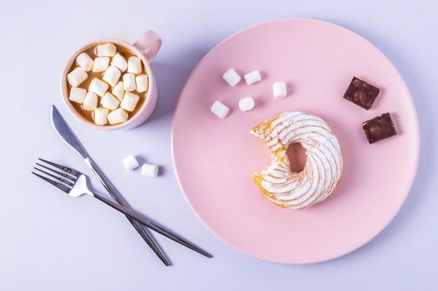 Widok z góry martwa natura ugryzionego ciasta na różowym talerzu, sztućce i kubek kakao z piankami. selektywna ostrość, orientacja pozioma.