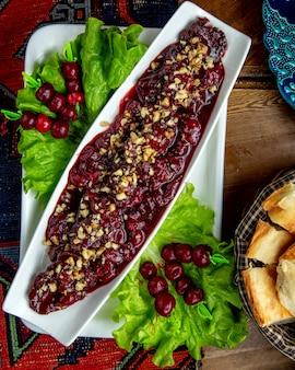 Widok z góry marynowanych owoców z orzechami ozdobionymi sałatą na stole
