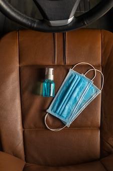 Widok z góry maska medyczna alkohol żel do dezynfekcji rąk na foteliku samochodowym.