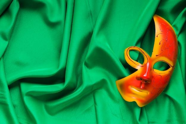 Widok z góry maski na karnawał na zielonej tkaninie