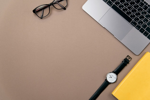 Widok z góry materiałów biurowych dla biznesu. laptop, żółty notatnik, okulary i zegarek na brązowym tle biurka.