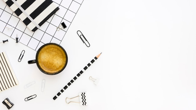 Widok z góry materiałów biurowych z ołówkiem i kawą