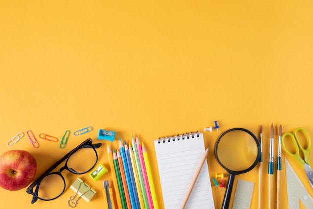 Widok z góry materiały biurowe lub szkolne na żółtym tle
