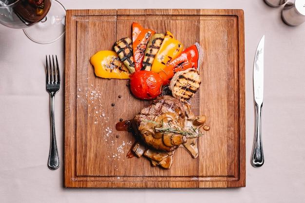 Widok z góry medalion ze stekiem w sosie grzybowym i grillowanymi warzywami