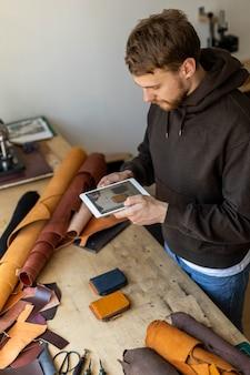 Widok z góry męski opalacz korzysta z tabletu w warsztacie skórzanym rzemieślnik tworzący promocję reklam online online