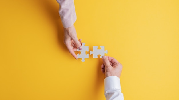 Widok z góry męskich i żeńskich rąk łączących dwa pasujące elementy układanki razem w koncepcyjnym obrazie. na żółtym tle.