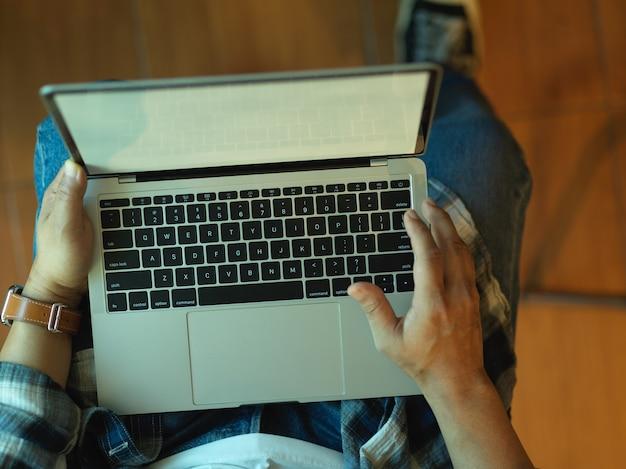 Widok z góry męskich rąk do pracy z laptopem na kolanach, siedząc w biurze