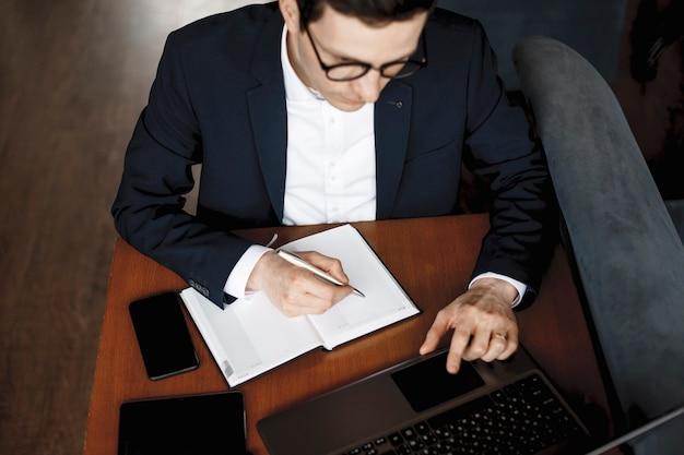 Widok z góry męskich rąk pracujących, podczas gdy dłoń trzymająca pióro na notebooku, podczas gdy inna na laptopie.