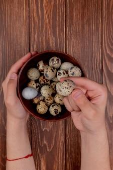 Widok z góry męskich rąk trzymając jaja przepiórcze na drewnianej misce z wieloma jajami przepiórczymi na drewnianym tle