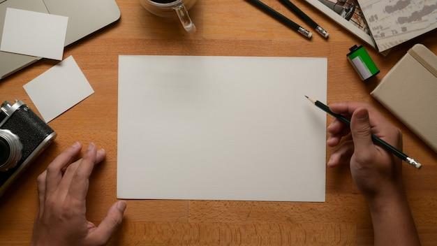 Widok z góry męskiego artysty pracującego z pustym szkicem, ołówkami, aparatem i materiałami eksploatacyjnymi na stole roboczym