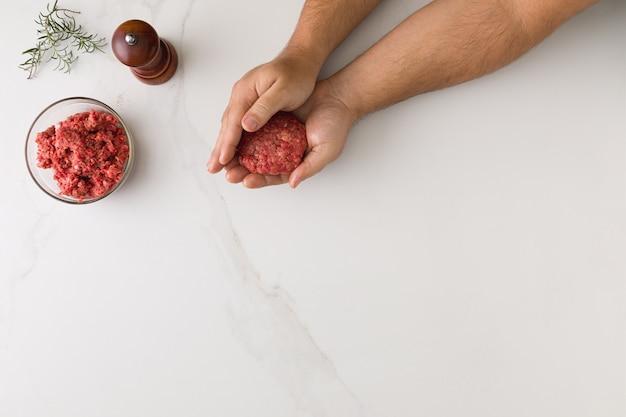Widok z góry męskiej dłoni formującej hamburgera na marmurowym stole, szklanej miski z mięsem, drewnianej młynka do pieprzu i rozmarynu z miejscem na tekst