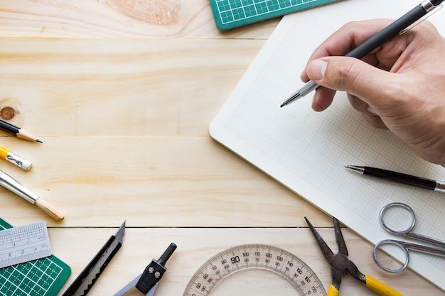 Widok z góry męskiej dłoni na stół z drewna z elementami narzędzi, sprzętu