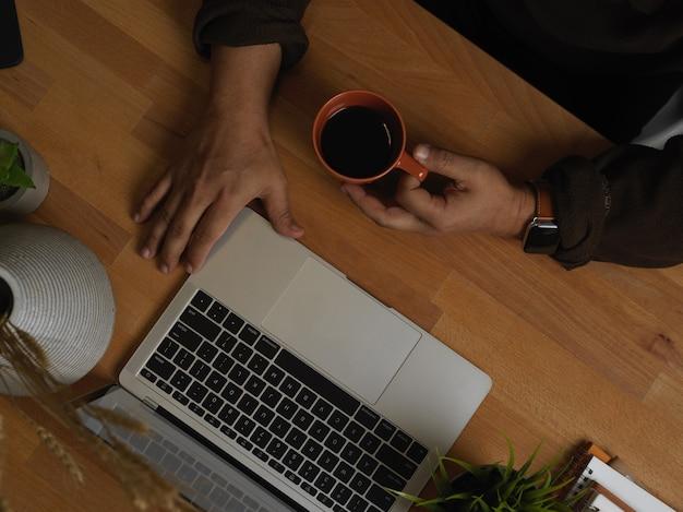 Widok z góry męskiej ręki trzymającej filiżankę kawy podczas pracy z laptopem w hone office room