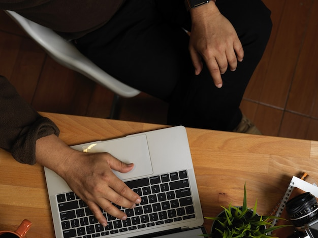 Widok z góry męskiej ręki wpisując na klawiaturze laptopa na drewnianym stole roboczym w biurze