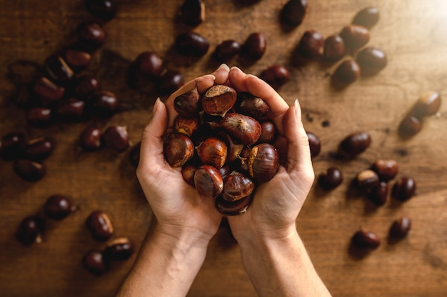 Widok z góry mężczyzna obie ręce trzymając kasztany, tło drewniany stół z większą ilością owoców.