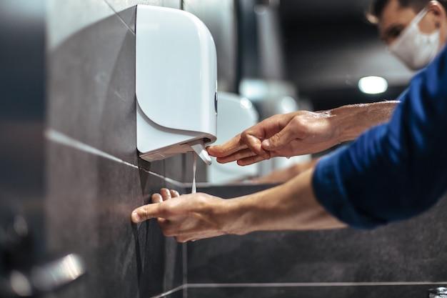 Widok z góry. mężczyzna ostrożnie myje ręce w łazience