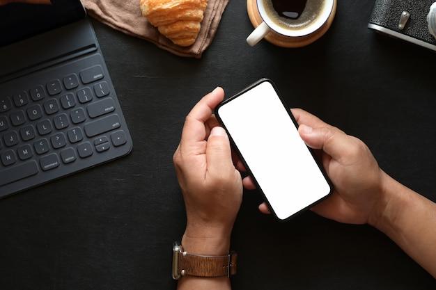Widok z góry mężczyzna ręka trzyma telefon komórkowy na obszarze roboczym