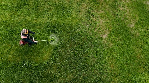 Widok z góry mężczyzna robotnik cięcia trawy z kosiarki.