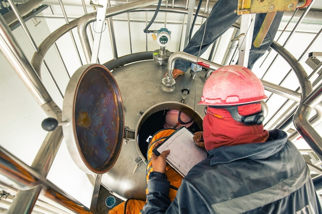 Widok z góry mężczyzna wspina się po schodach do zbiornika strefa chemiczna ze stali nierdzewnej dmuchawa bezpieczeństwa w przestrzeni zamkniętej świeże powietrze