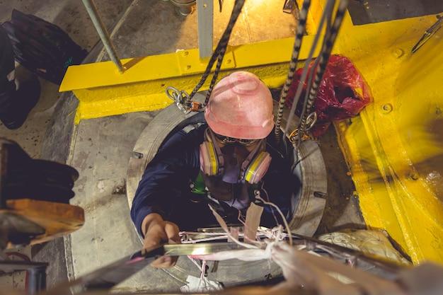 Widok z góry mężczyzna wspina się po schodach do zbiornika strefa chemiczna ze stali nierdzewnej ograniczona przestrzeń ratuje życie dzięki bezpieczeństwu liny ratunkowej