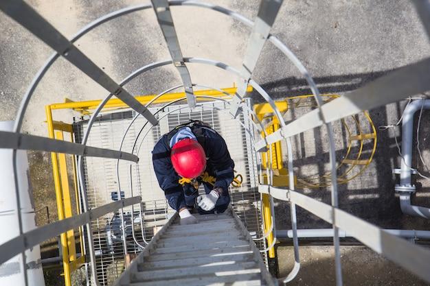 Widok z góry mężczyzna wspina się po zimnym zbiorniku do przechowywania drabiny