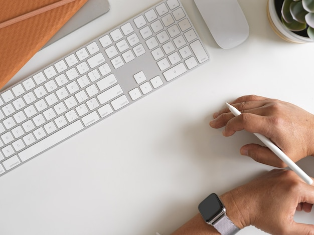 Widok z góry mężczyzny trzymającego rysik w ręku na biurku komputera z klawiaturą, myszą i materiałami eksploatacyjnymi