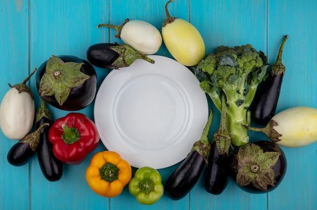 Widok z góry miejsca kopiowania biały talerz z kolorową papryką i brokułami z bakłażanem na turkusowym tle